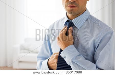 people, business, fashion and clothing concept - close up of man in shirt dressing up and adjusting tie on neck over living room background