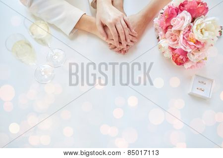 people, homosexuality, same-sex marriage and love concept - close up of happy lesbian couple hands with flower bunch, champagne glasses and wedding rings over holiday lights background