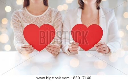 people, homosexuality, same-sex marriage, valentines day and love concept - close up of happy lesbian couple holding red paper hearts over holiday lights background