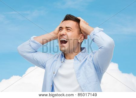 stress, headache, health care and people concept - unhappy man with closed eyes touching his forehead over blue sky and cloud background