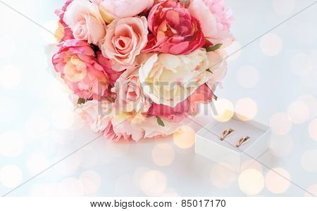 people, homosexuality, same-sex marriage and love concept - close up of gay female wedding rings in little box and flower bunch on table over holiday lights background