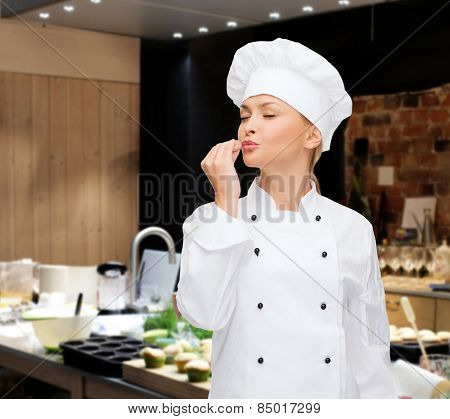 cooking, bakery, gesture and food concept - smiling female chef showing delicious gesture over restaurant kitchen background
