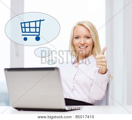 business, people, sale, gesture and technology concept - smiling businesswoman or student showing thumbs up with laptop computer and shopping trolley in text bubble at office