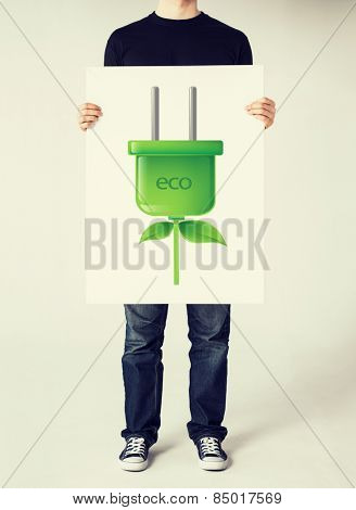 close up of hands holding picture of green electrical eco plug