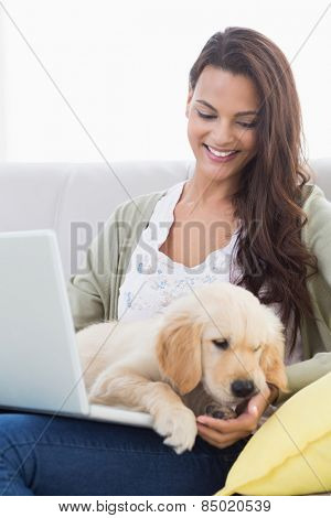 Happy beautiful woman with dog using laptop on sofa at home