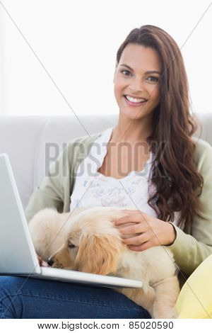 Portrait of happy beautiful woman with dog using laptop on sofa at home