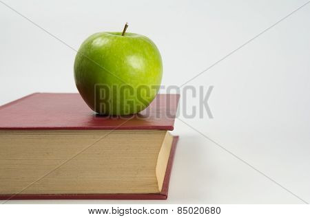 Green apple on a book