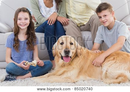 Portrait of siblings with dog and parents sitting behind at home