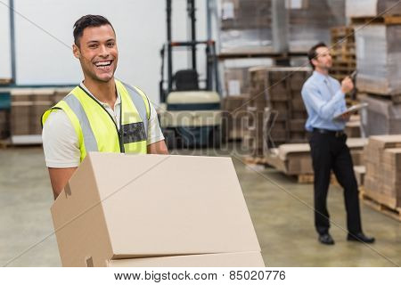 Smiling warehouse worker moving boxes on trolley in a large warehouse