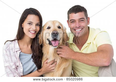 Portrait of happy loving couple stroking dog over white background