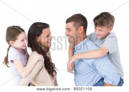 Side view of happy parents giving piggyback ride to children over white background