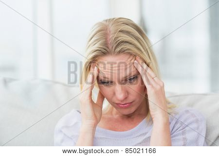 Upset woman rubbing her temples in living room
