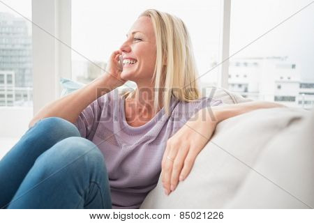 Smiling woman talking on mobile phone on sofa at home