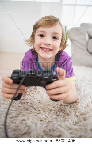 Portrait of happy boy playing video game while lying on rug at home