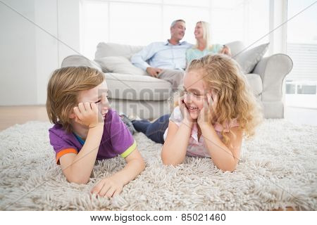 Happy siblings looking at each other while parents sitting on sofa at home