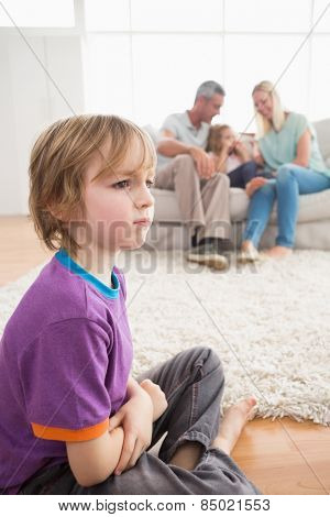 Sad boy sitting on floor while parents enjoying with sister on sofa at home