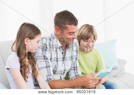 Man telling story to daughter and son while sitting on sofa at home