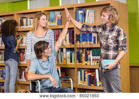 College students high fiving in the library