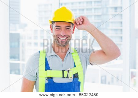 Portrait of happy manual worker wearing yellow hard hat in bright office