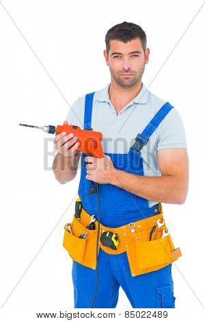 Portrait of confident male carpenter in overall holding drill machine on white background