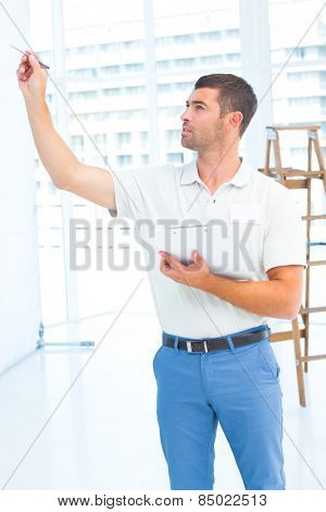 Male supervisor with clipboard inspecting at construction site