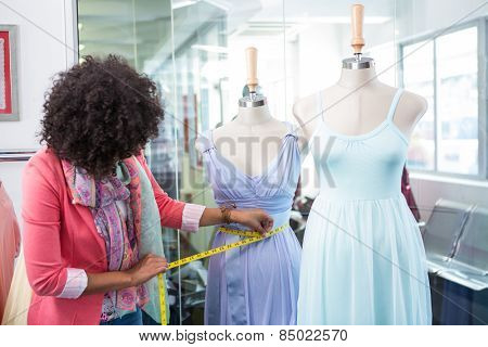 Female fashion designer measuring dummy waist