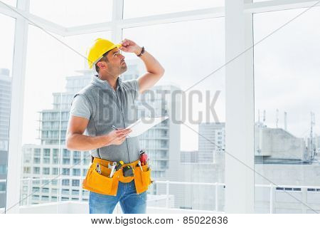 Handyman holding clipboard while inspecting building