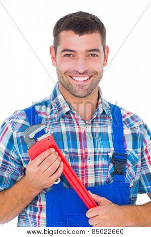 Portrait of confident male repairman holding monkey wrench on white background