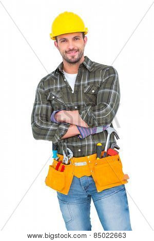 Smiling handyman wearing tool belt on white background