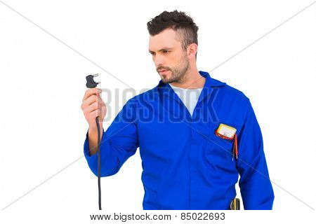 Electrician looking at plug on white background