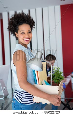 Portrait of beautiful casual woman carrying her belongings in box