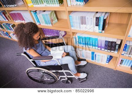 Smiling disabled student in library reading book at the university