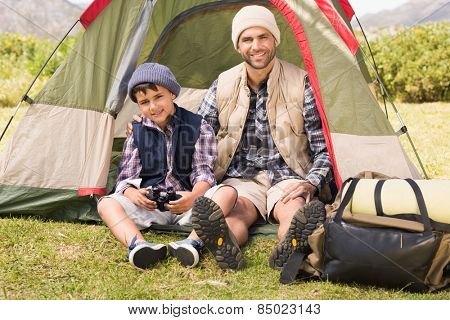 Father and son beside their tent on a sunny day