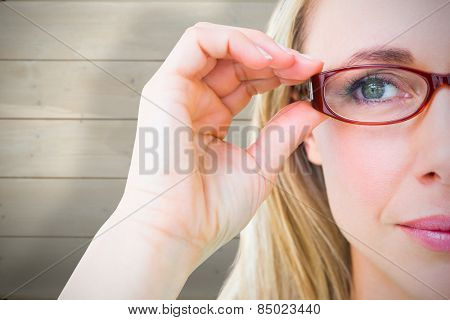 Close up of pretty blonde with red reading glasses against bleached wooden planks background