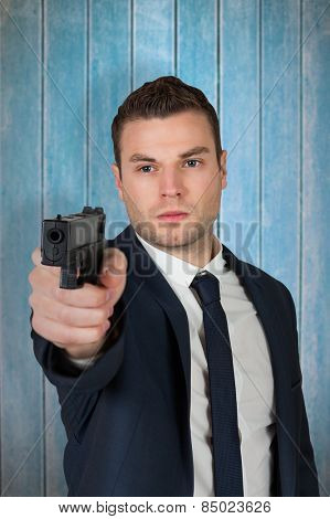 Serious businessman pointing a gun against wooden planks
