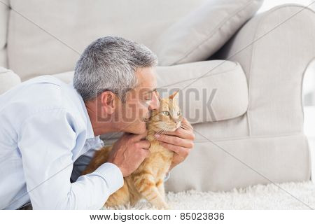 Side view of man kissing cat by sofa at home
