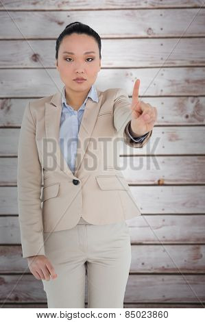 Unsmiling asian businesswoman pointing against wooden planks