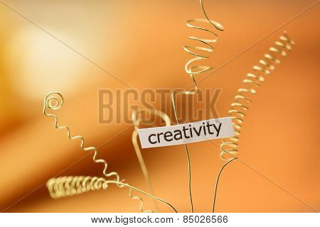 Bursting creativity. Creativity expressed with gold wire abstract. Extremely shallow depth of field due to subject size..
