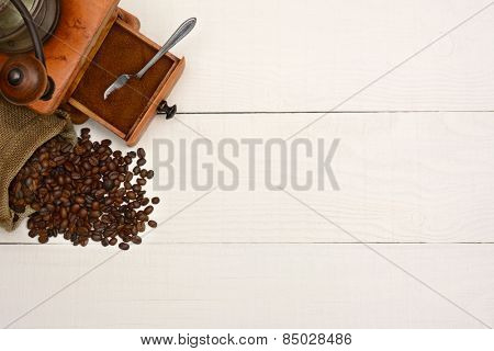 High angle shot of a bag of coffee beans and an antique  grinder on a rustic white wood table. The items are in the upper left corner leaving room for your copy.