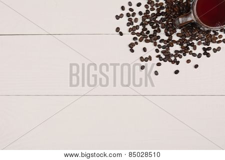 High angle shot of a coffee mug and fresh roasted beans in the corner of the frame on a white wood table. Horizontal format with copy space.