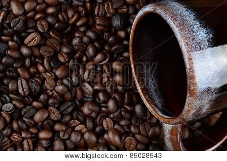 High angle closeup of a coffee mug laying on a bed of fresh roasted beans. Only part of the ceramic cup is showing.