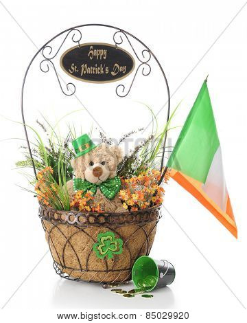 A basket filled with orange and green foliage, toy bear with green tie and hat, and an Irish flag.  The basket's  handle is adorned with a