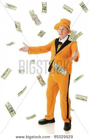 A flamboyant senior man wearing an orange tuxedo and hat, tossing or catching falling 100, 50 and 20 dollar bills.  On a white background.