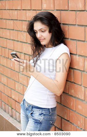 Young Woman At Brick Wall Typing Message