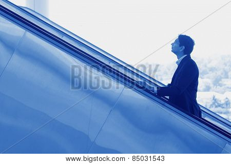 Asian Indian businessman ascending escalator, side view in blue tone.