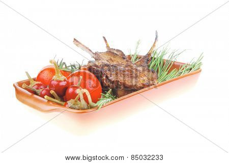 meat portion : ribs on plate served with fresh cherry tomatoes and raw vegetables and chives . shallow dof