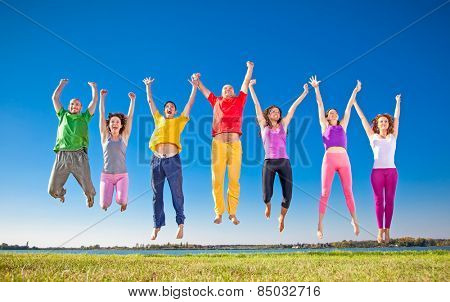 Happy smiling  group of jumping  people on banch of lake in Serbia.