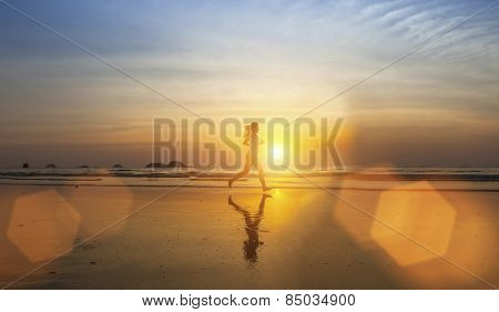 Young girl silhouette Jogging on sea beach in rays of the sunset.
