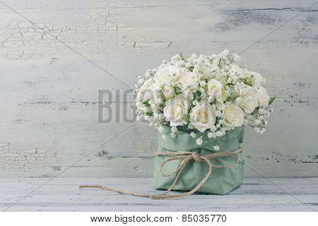 White roses in a green bag