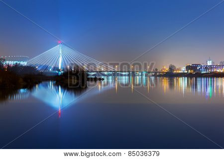 Vistula river scenery with cable-stayed illuminated bridge in Warsaw, Poland